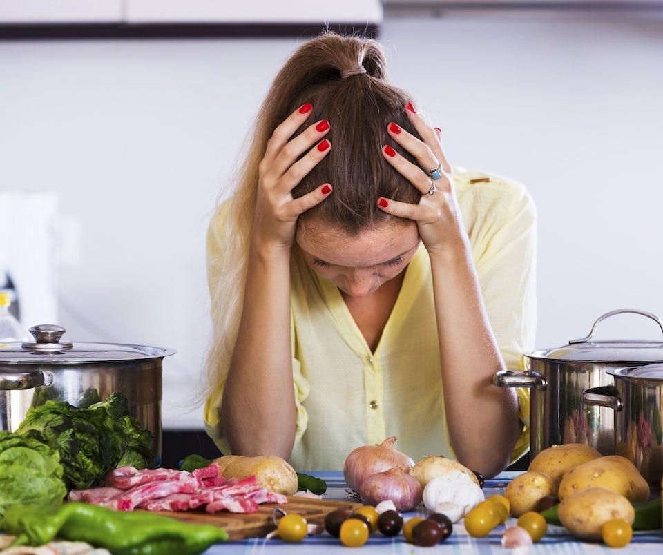 Kvinna med huvudvärk. Mat i förgrunden.