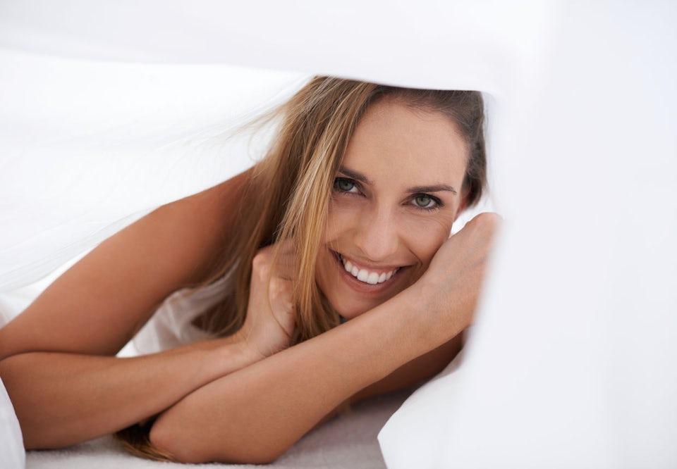 Nainen makaa vatsallaan sängyssä ja hymyilee
