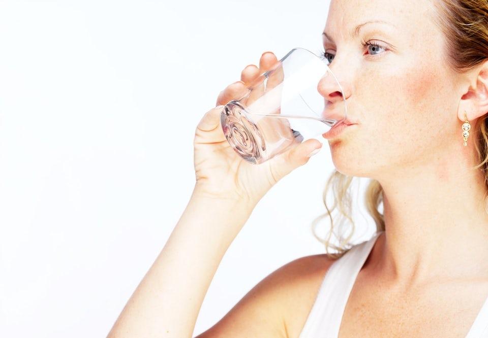 Nainen juo vettä lasista