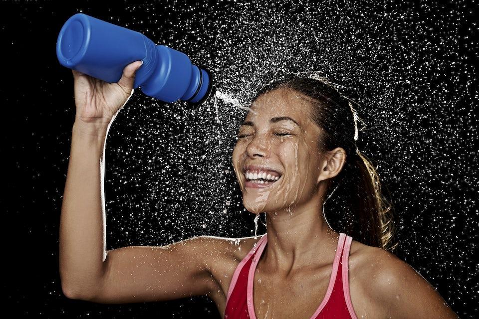 Nainen ruiskuttaa vettä kasvoilleen juomapullosta