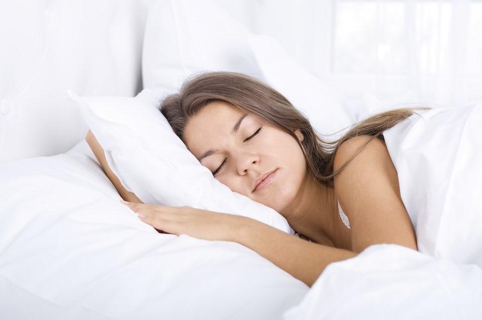 Kvinna sover i säng.