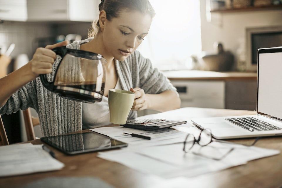 Kvinne heller kaffe i kopp på jobben