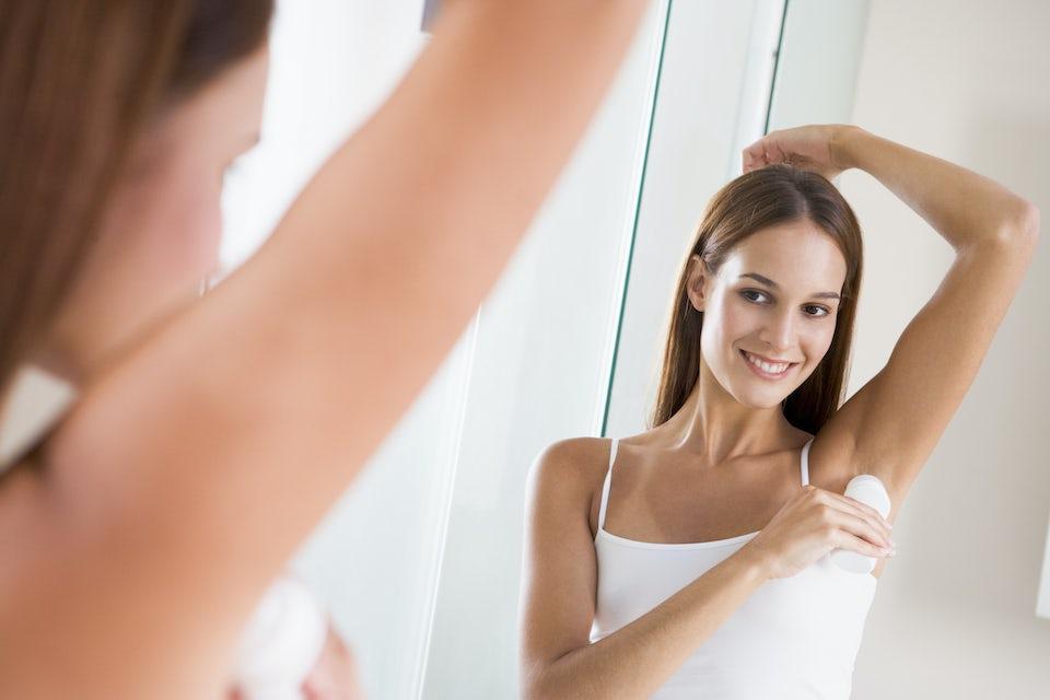 Kvinna tar på deodorant.