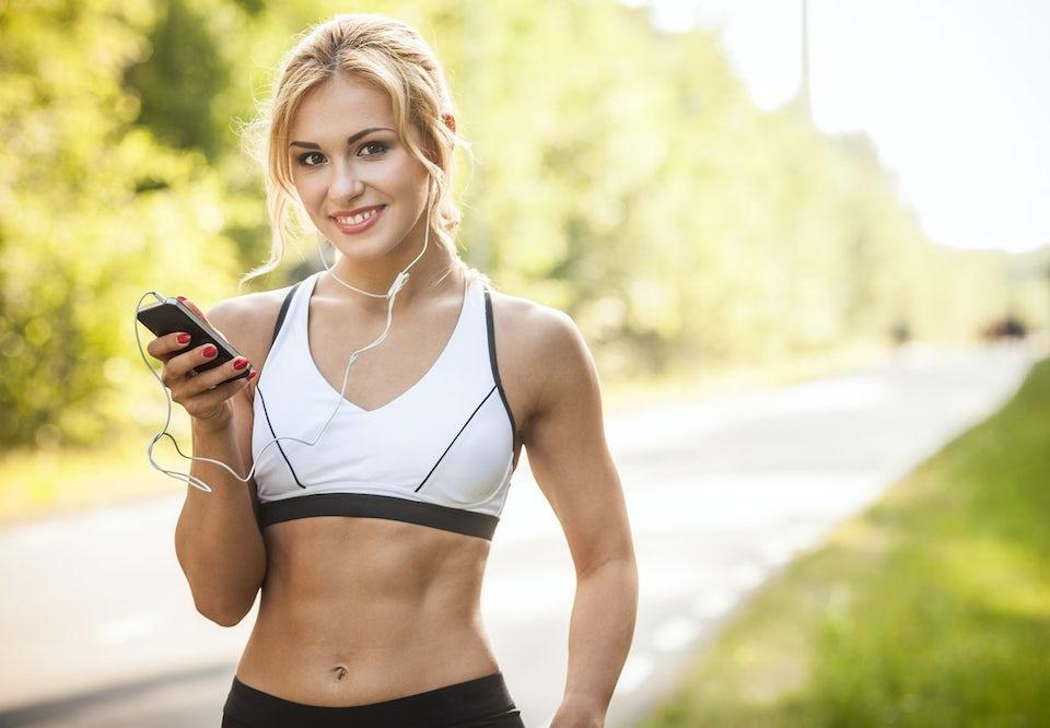Kvinne i sports-BH med telefon i hånden