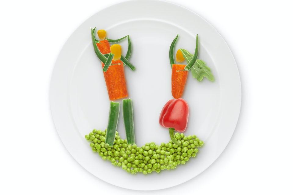 Vihanneksista tehtyjä ihmishahmoja lautasella