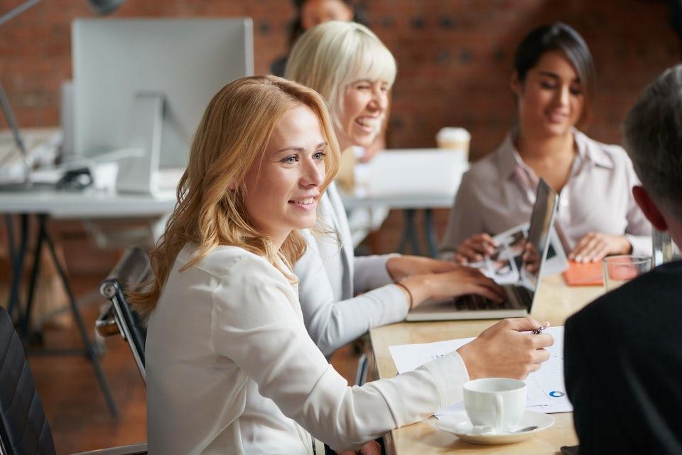 Nainen istuu pöydän ympärillä kollegoiden kanssa