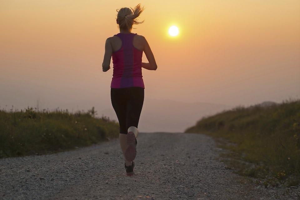 Kvinna springer på stig mot solnedgång.