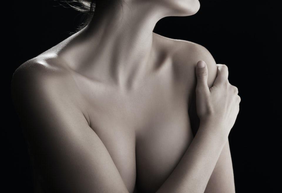 Nainen käsi rintojensa peittona