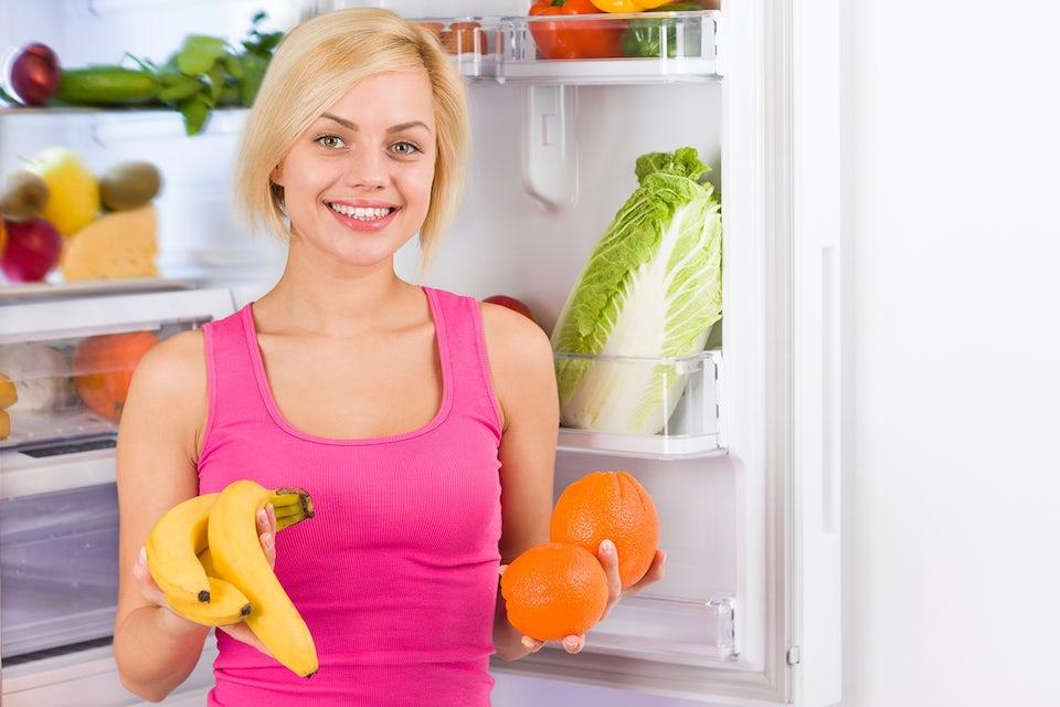 Kvinne står foran kjøleskap med frukt i hendene