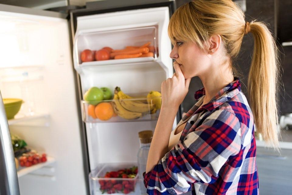 Nainen seisoo jääkaapin edessä hedelmiä käsissään
