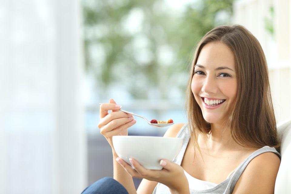 Kvinna äter med en skål i handen.