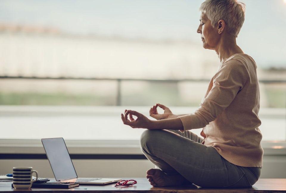 Kvinde mediterer, computer og kaffekop ved siden af
