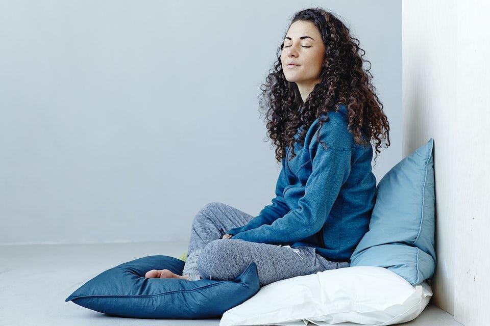 Nainen istuu silmät kiinni tyynyjen päällä risti-istunnassa