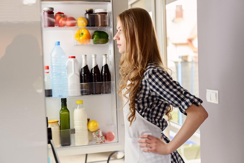 Kvinna kikar in i ett kylskåp.