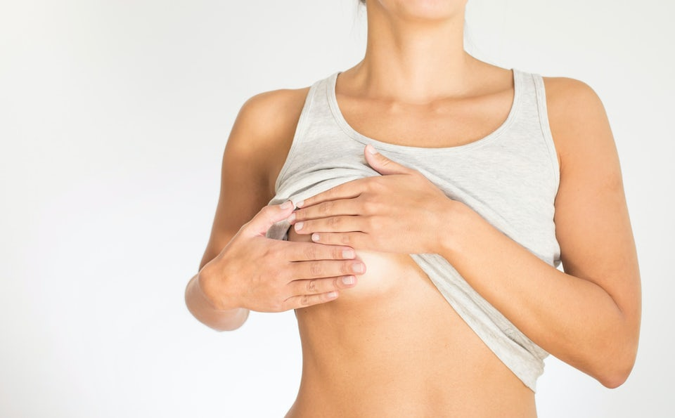 Nainen tutkii rintansa rintasyövän varalta
