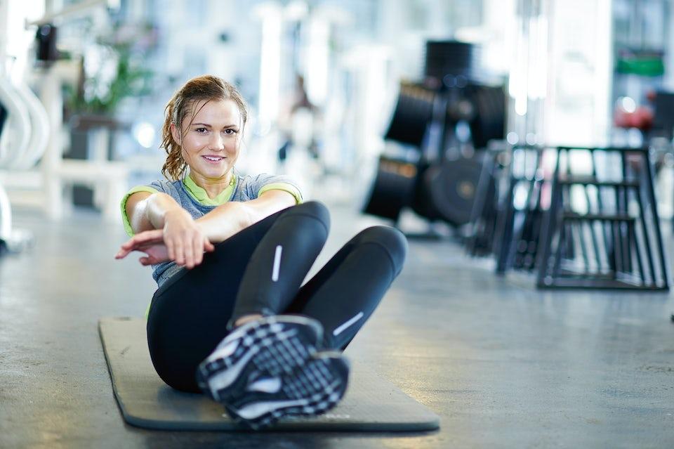 Kvinde laver træningsøvelse på måtte.