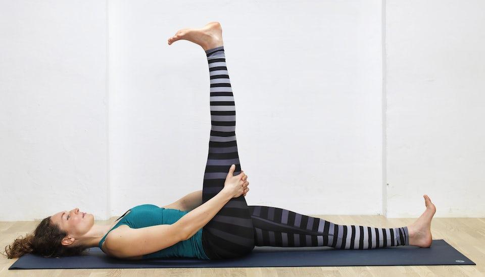 Yogainstruktør Susanne Lidang viser, hvordan man laver yogaøvelsen Liggende hasestræk.