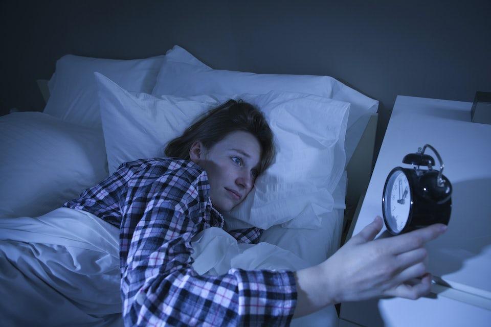 Kvinne ligger i sengen og ser på vekkerklokka