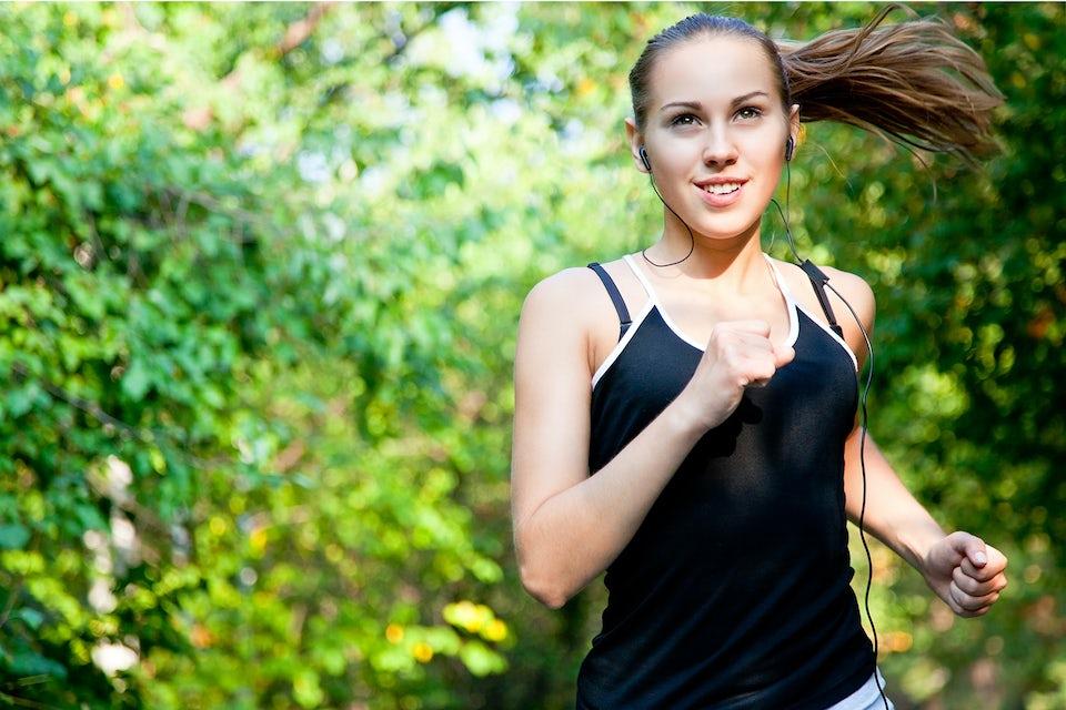 Kvinna springer i skogen.