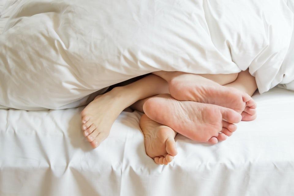 pariskunnan jalat pilkistävät peiton alta