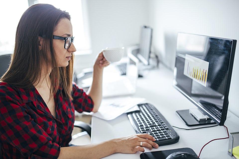 Kvinne sitter foran pc-en på jobb og drikker en kopp kaffe.
