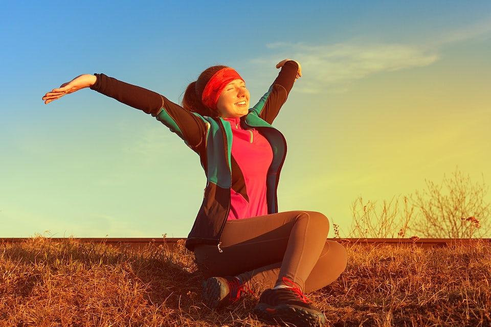 Kvinna sträcker på sig i naturen med soluppgång.