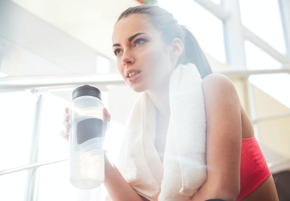 Kvinna dricker vatten på gymmet.
