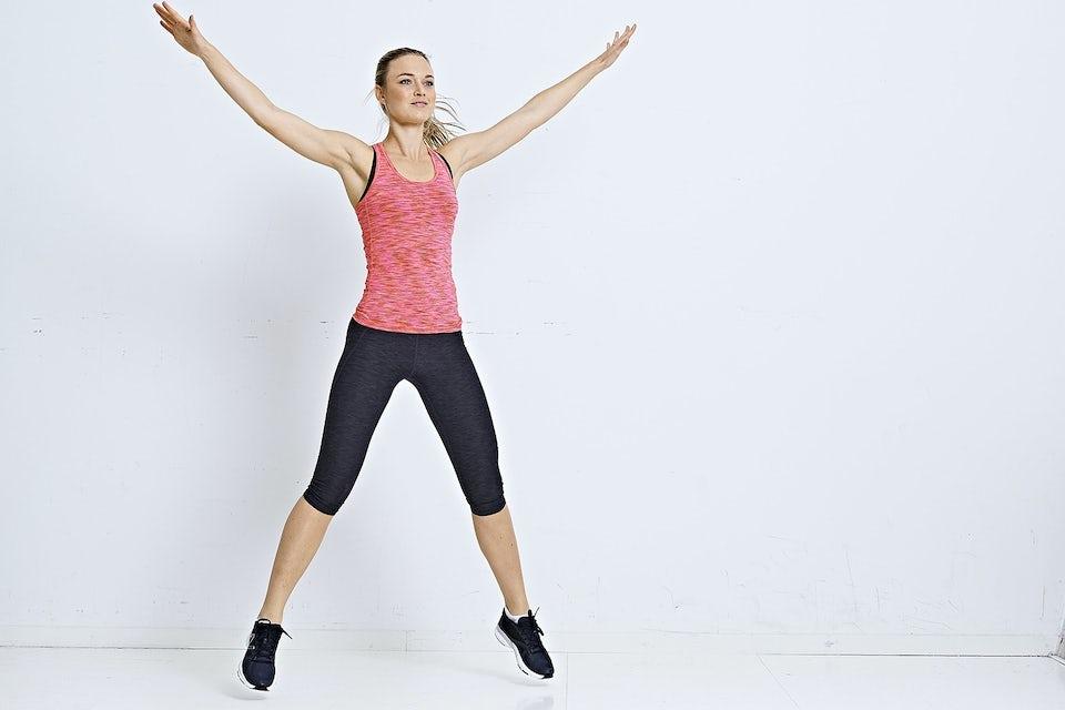 Kvinna gör jumping jacks, vit bakgrund.