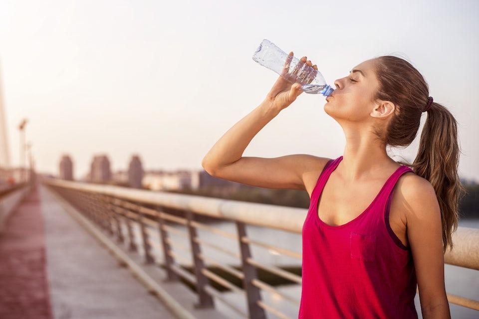 Kvinna i rött linne dricker vatten.