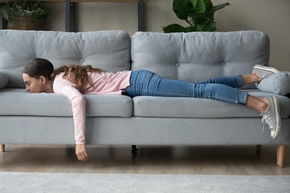 Kvinde ligger energiforladt på sofa