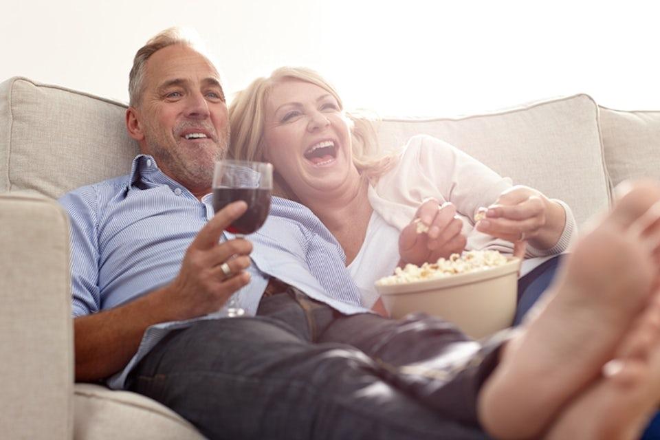 Förälskat par äter pizza i soffan.