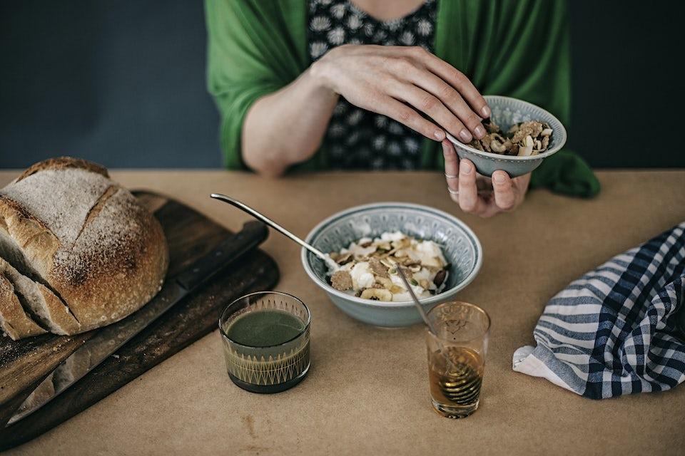 Kvinna gör klart sin frukost. Yoghurt med müsli och bröd.