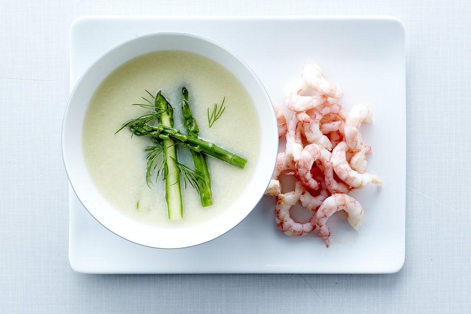 Tallrik med räkor och skål med soppa.