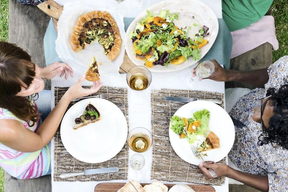 Kaksi naista istuu ruokapöydän ääressä