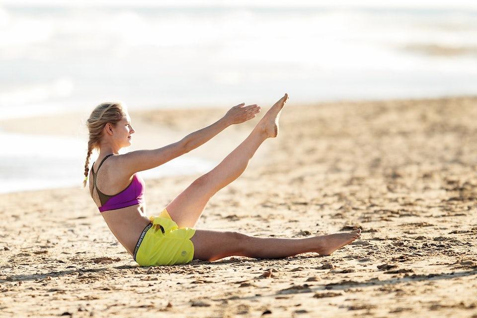 Kvinne gjør magekryssbøyning på stranden. Sirkeltrening.