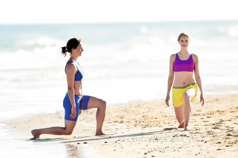 Kaksi naista tekee askelkyykkyä rannalla. Kiertoharjoittelu