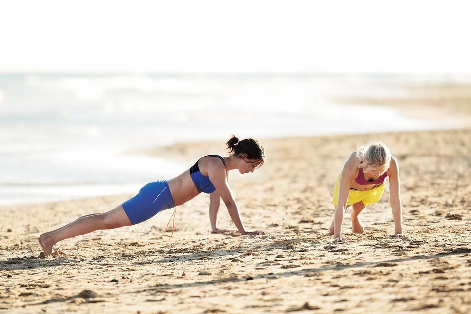 Kvinnor gör armhävningar på stranden. Cirkelträning.