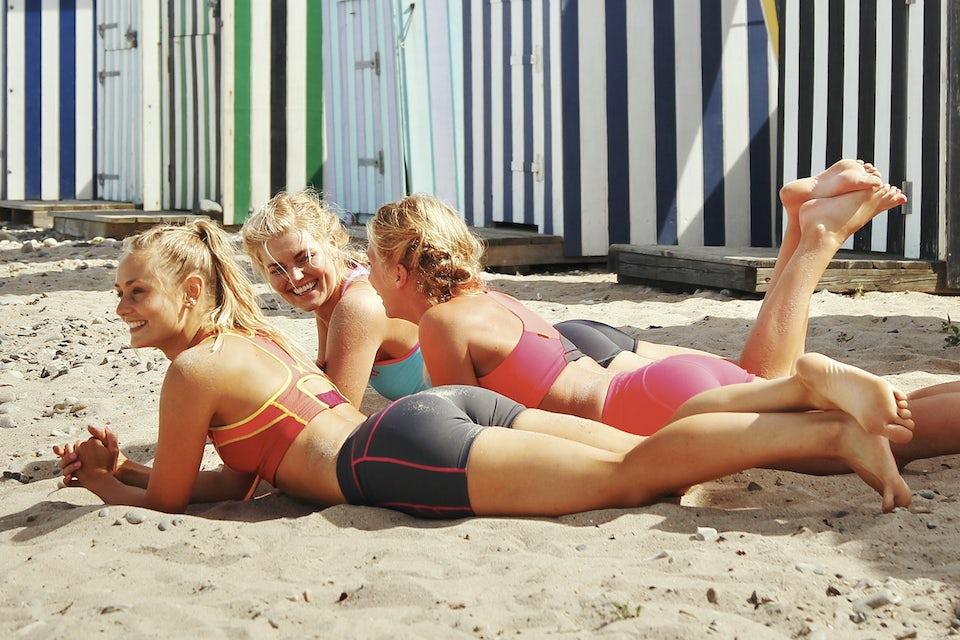 jenter ligger på stranden i sanden og smiler