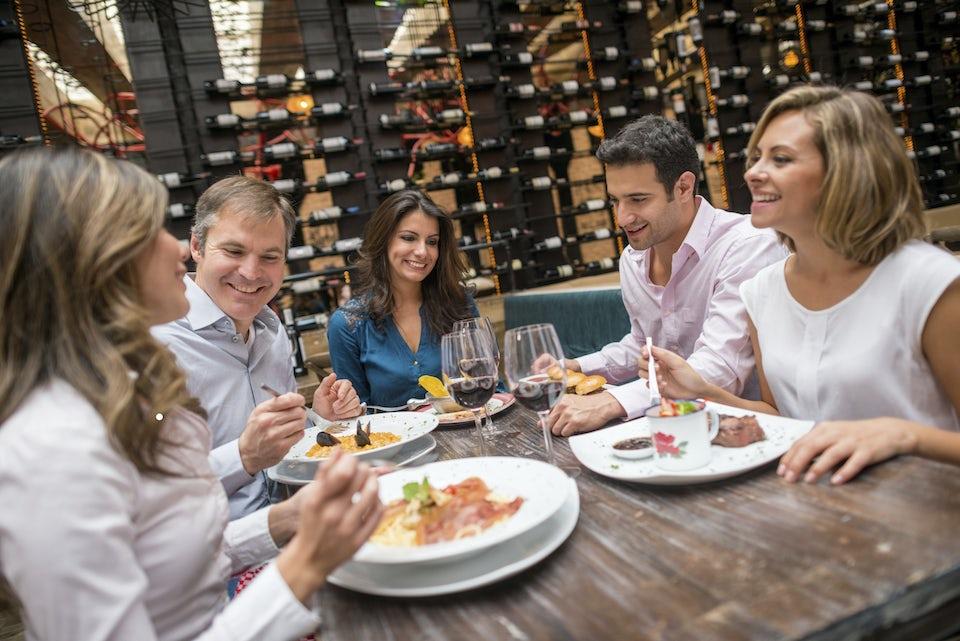 Viisi ihmistä hymyilee ravintolassa annostensa äärellä