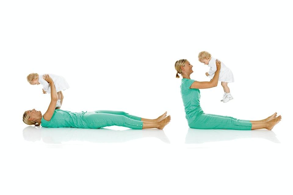 Nainen tekee istumaannousua vauva käsissään