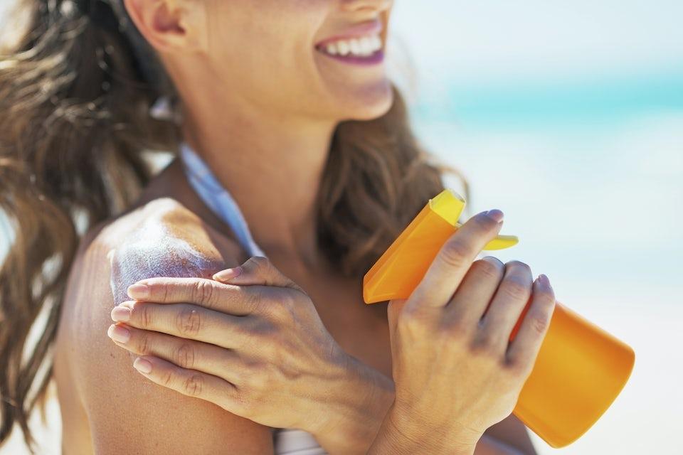 Nainen levittää aurinkovoidetta suihkepullosta rannalla
