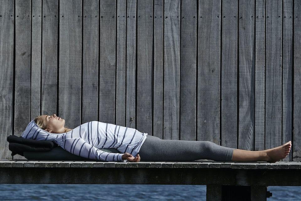 Kvinna ligger på brygga.