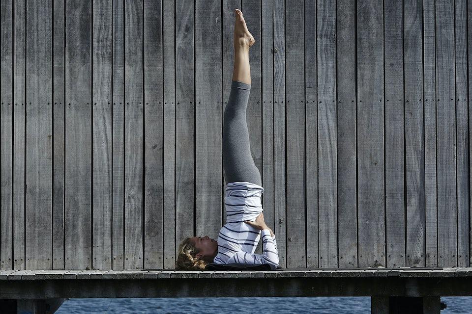 Kvinna gör yoga på brygga.