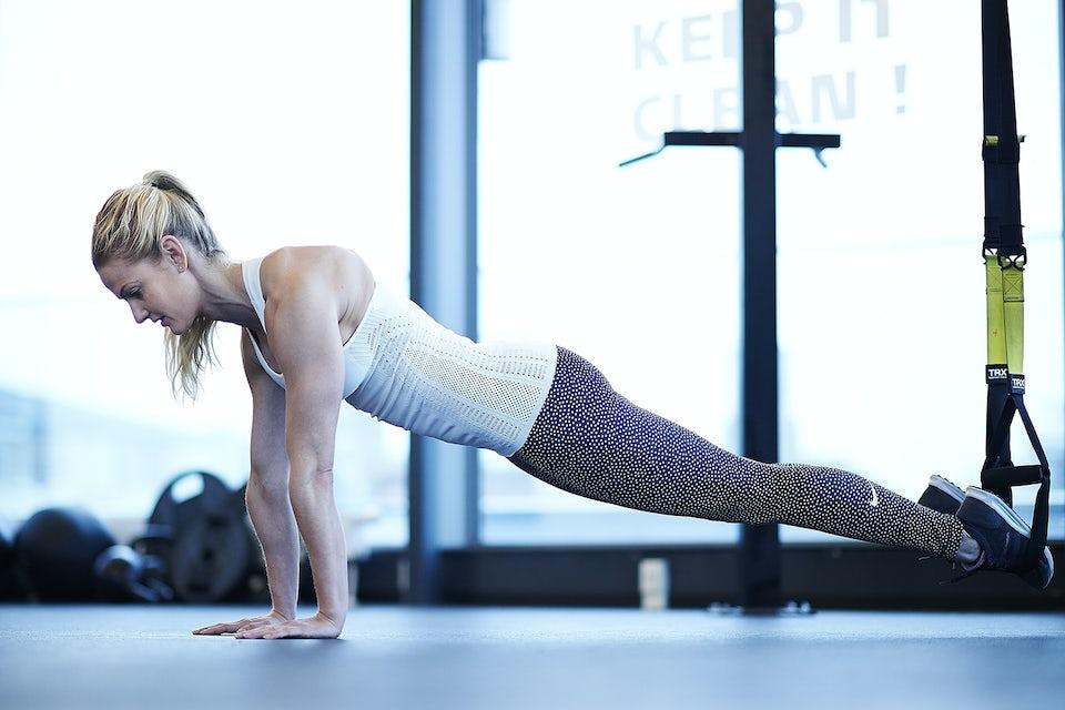 Kvinna tränar med TRX. Styrketräning.