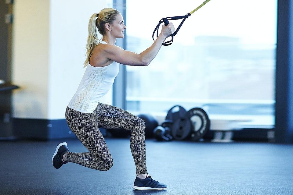 Kvinna tränar sidohopp med TRX.