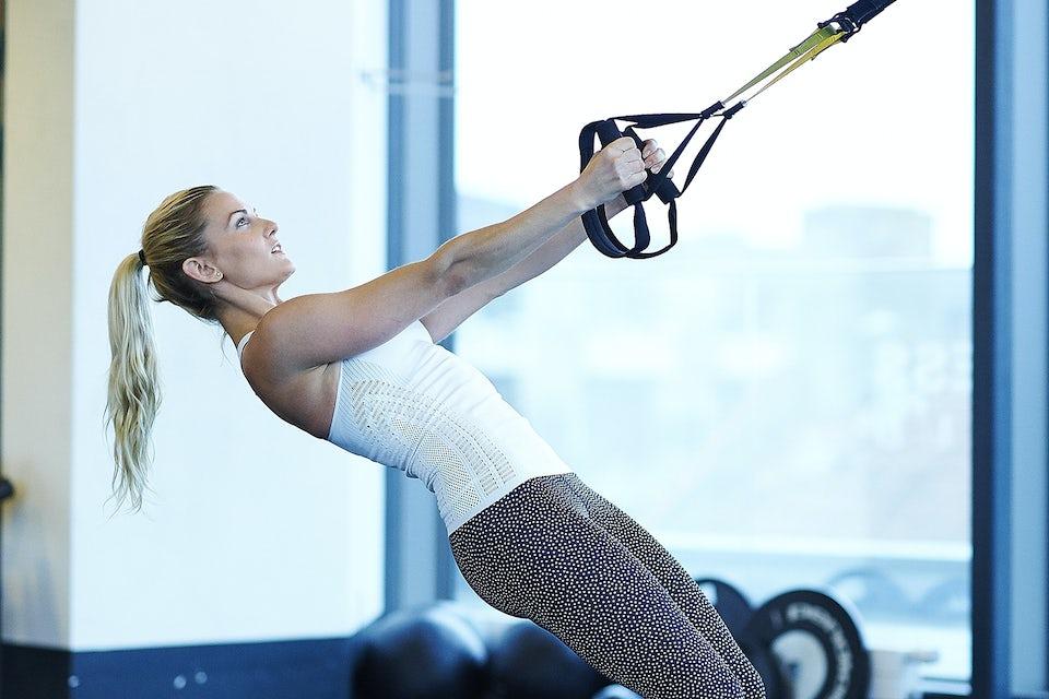 Pige træner med TRX.
