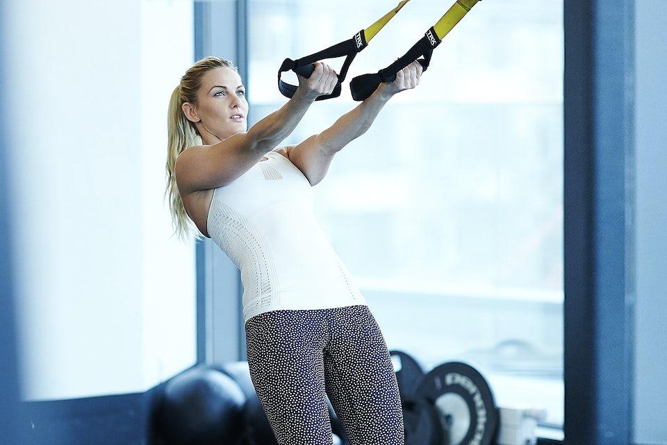Pige træner TRX i fitnesscenter.