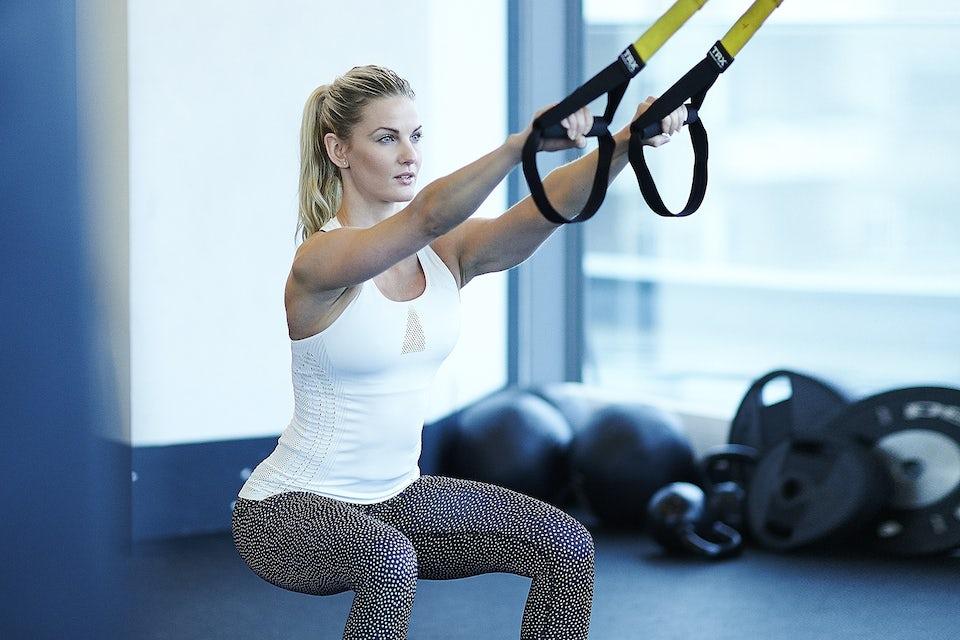 Kvinna gör squat jump med TRX.