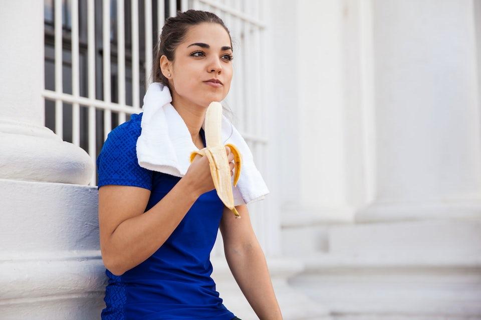 Stærk kvinde spiser banan efter træning