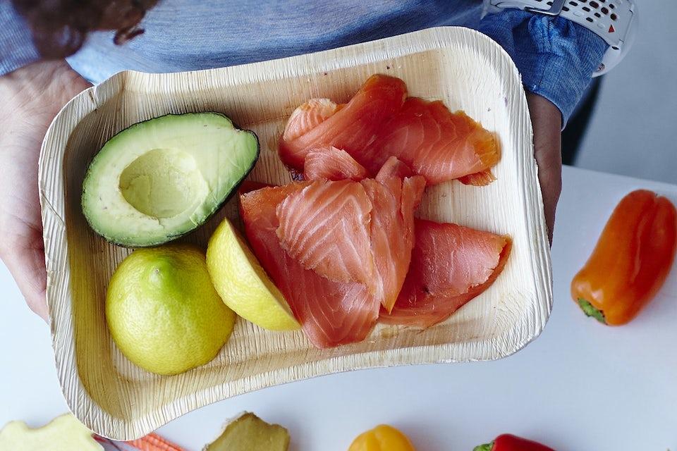 tallerken med laks og avocado og citroner.